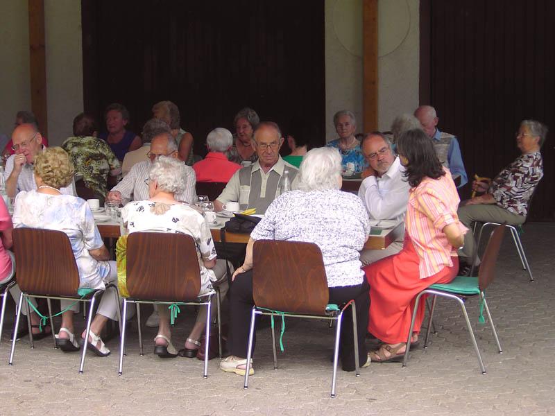 Bild vom Seniorenkaffee unter der Überdachung am Feuerwehrgerätehaus, die Organisatorin unterhält sich mit Pfarrer Löhde